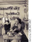 Positive craftsman talking to colleague in ceramics studio. Стоковое фото, фотограф Яков Филимонов / Фотобанк Лори
