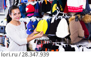 Купить «Woman choosing new knit cap», фото № 28347939, снято 22 ноября 2016 г. (c) Яков Филимонов / Фотобанк Лори
