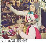 Купить «glad mother with little daughter buying decorations for Xmas», фото № 28356067, снято 21 сентября 2018 г. (c) Яков Филимонов / Фотобанк Лори