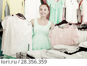 Купить «Young woman shopper choosing garments at sales», фото № 28356359, снято 19 июня 2017 г. (c) Яков Филимонов / Фотобанк Лори
