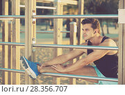 Купить «Male athlete stretching on outdoor fitness station», фото № 28356707, снято 14 августа 2017 г. (c) Яков Филимонов / Фотобанк Лори