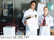 Купить «Two smiling employees standing in packaging section on wine manufactory», фото № 28356747, снято 21 сентября 2016 г. (c) Яков Филимонов / Фотобанк Лори