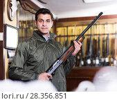 Handsome male hunter choosing shotgun in store. Стоковое фото, фотограф Яков Филимонов / Фотобанк Лори