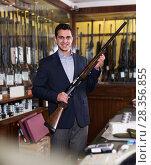 Positive salesman in hunting shop demonstrating shotgun. Стоковое фото, фотограф Яков Филимонов / Фотобанк Лори