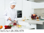 Купить «Female cook is making salad on her work place in the kitchen», фото № 28356979, снято 3 апреля 2018 г. (c) Яков Филимонов / Фотобанк Лори