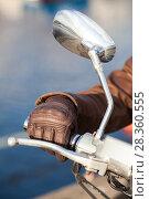 Купить «Мотоциклист держит ручку газа в коричневой кожаной перчатке, крупный план с зеркалом заднего вида», фото № 28360555, снято 30 апреля 2018 г. (c) Кекяляйнен Андрей / Фотобанк Лори