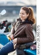 Купить «Улыбающаяся девушка в коричневой кожаной куртке сидит на мотоцикле», фото № 28360575, снято 30 апреля 2018 г. (c) Кекяляйнен Андрей / Фотобанк Лори