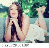 Купить «Cheerful young female is posing on bench in her free time», фото № 28361391, снято 10 июня 2017 г. (c) Яков Филимонов / Фотобанк Лори