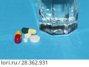 Купить «Таблетки, капсулы и стакан воды на синем фоне крупным планом», фото № 28362931, снято 4 мая 2018 г. (c) Ирина Носова / Фотобанк Лори