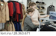 Купить «Happy teen girl looking for new clothing with her mum during family shopping», видеоролик № 28363671, снято 26 апреля 2018 г. (c) Яков Филимонов / Фотобанк Лори