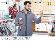 Купить «Man choosing new glue gun», фото № 28369787, снято 5 апреля 2017 г. (c) Яков Филимонов / Фотобанк Лори