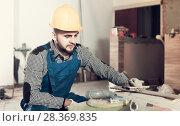 Купить «Builder is preparing for repair in the room at object.», фото № 28369835, снято 3 июня 2017 г. (c) Яков Филимонов / Фотобанк Лори