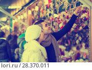 Купить «Couple choosing Christmas decoration», фото № 28370011, снято 12 ноября 2019 г. (c) Яков Филимонов / Фотобанк Лори
