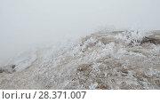 Купить «Movement on a stony mountain slope. The rocks and grass are covered with hoarfrost.», видеоролик № 28371007, снято 26 марта 2018 г. (c) Андрей Радченко / Фотобанк Лори