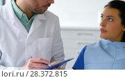 Купить «dentist and patient talking at dental clinic», видеоролик № 28372815, снято 26 апреля 2018 г. (c) Syda Productions / Фотобанк Лори