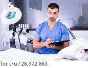 Portrait of professional cosmetician working with papers in clinic of esthetic cosmetology. Стоковое фото, фотограф Яков Филимонов / Фотобанк Лори