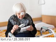 Купить «Visually impaired elderly 95 years old woman sitting at the bad trying to read with magnifying glass.», фото № 28388091, снято 5 апреля 2020 г. (c) Matej Kastelic / Фотобанк Лори