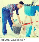 Купить «Craftsman is going to mix putty», фото № 28388567, снято 21 мая 2017 г. (c) Яков Филимонов / Фотобанк Лори