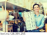 Купить «Woman customer holding decorative vase», фото № 28391255, снято 22 ноября 2017 г. (c) Яков Филимонов / Фотобанк Лори