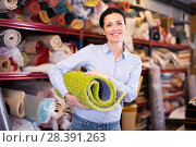 Купить «Cheerful woman customer shopping carpet in store», фото № 28391263, снято 22 ноября 2017 г. (c) Яков Филимонов / Фотобанк Лори