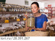 Купить «adult female take a smell natural dried herbs sold by weight in eco shop», фото № 28391267, снято 13 июня 2017 г. (c) Яков Филимонов / Фотобанк Лори