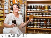 Купить «Smiling mature female customer holding honey jar», фото № 28391311, снято 15 декабря 2018 г. (c) Яков Филимонов / Фотобанк Лори