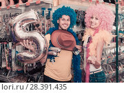 Купить «Family couple preparing for fest and choosing clown wigs», фото № 28391435, снято 11 апреля 2017 г. (c) Яков Филимонов / Фотобанк Лори
