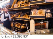 Купить «Male shop assistant demonstrating delicious loaves of bread in bakery», фото № 28393831, снято 26 января 2017 г. (c) Яков Филимонов / Фотобанк Лори
