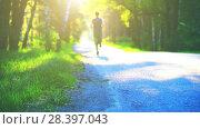 Купить «Sport man running at asphalt road. Rural city park. Green tree forest and sun rays on horizon.», видеоролик № 28397043, снято 16 апреля 2018 г. (c) Александр Маркин / Фотобанк Лори