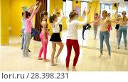 Купить «Group of children participating in dance class, following their teacher in dance school», видеоролик № 28398231, снято 26 марта 2018 г. (c) Яков Филимонов / Фотобанк Лори