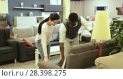 African man with his wife are choosing new sofa for their home in the store. Стоковое видео, видеограф Яков Филимонов / Фотобанк Лори