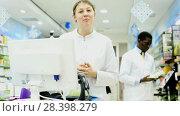 Купить «Experienced female pharmacist standing on background with male colleague in pharmacy», видеоролик № 28398279, снято 28 марта 2018 г. (c) Яков Филимонов / Фотобанк Лори