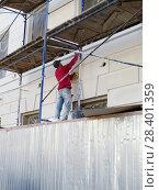 Рабочий-гастарбайтер стоит на строительных лесах и штукатурит фасад здания. Стоковое фото, фотограф ViktoriiaMur / Фотобанк Лори