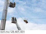 Купить «Эвакуация пострадавшего. Бойцы пожарной охраны в люльках на выдвижных лестницах», эксклюзивное фото № 28401431, снято 24 июня 2017 г. (c) Александр Щепин / Фотобанк Лори