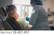 Купить «Little girl on reception at the dentist, the stomatologist cleaning and watering the child's teeth, girl smiling», фото № 28401451, снято 19 июня 2019 г. (c) Константин Шишкин / Фотобанк Лори