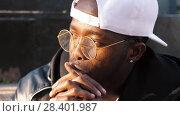 Купить «Young afro man thinking», видеоролик № 28401987, снято 25 апреля 2018 г. (c) Илья Шаматура / Фотобанк Лори