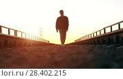 Купить «Man walking at sunset», видеоролик № 28402215, снято 26 апреля 2018 г. (c) Илья Шаматура / Фотобанк Лори