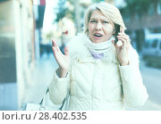 Купить «Female in the city in scarf and jacket talking on phone», фото № 28402535, снято 21 декабря 2017 г. (c) Яков Филимонов / Фотобанк Лори