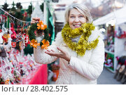 Купить «Adult woman is choosing Christmas wreath for house in the market», фото № 28402575, снято 21 декабря 2017 г. (c) Яков Филимонов / Фотобанк Лори