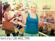 Купить «girl showing a chosen pair of shoes», фото № 28402795, снято 25 апреля 2019 г. (c) Яков Филимонов / Фотобанк Лори