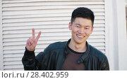 Купить «Chinese man showing peace sign», видеоролик № 28402959, снято 25 апреля 2018 г. (c) Илья Шаматура / Фотобанк Лори