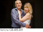 Купить «Couple with Age Difference Hugging on Black Background. Attractive Young Woman in Dress and Senior Man in Blue Shirt Embracing and Looking at the Camera», фото № 28405691, снято 9 октября 2017 г. (c) Ольга Балынская / Фотобанк Лори
