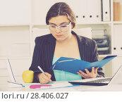 Office manager woman is reading documents before signing it. Стоковое фото, фотограф Яков Филимонов / Фотобанк Лори