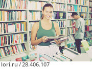Купить «Interested teenager girl customer reading book», фото № 28406107, снято 16 сентября 2016 г. (c) Яков Филимонов / Фотобанк Лори