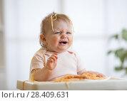 Купить «Cute messy baby crying while eating pasta at home», фото № 28409631, снято 18 июня 2019 г. (c) Оксана Кузьмина / Фотобанк Лори