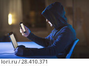 hacker with laptop and smartphone in dark room. Стоковое фото, фотограф Syda Productions / Фотобанк Лори