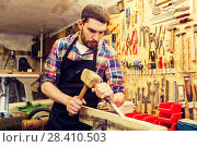 Купить «carpenter with wood, hammer and chisel at workshop», фото № 28410503, снято 14 мая 2016 г. (c) Syda Productions / Фотобанк Лори