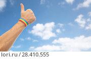Купить «hand with gay pride rainbow wristband shows thumb», фото № 28410555, снято 2 ноября 2017 г. (c) Syda Productions / Фотобанк Лори