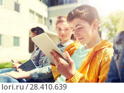 Купить «happy friends or students with tablet pc outdoors», фото № 28410639, снято 21 мая 2016 г. (c) Syda Productions / Фотобанк Лори