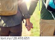 Купить «close up of couple with backpacks holding hands», фото № 28410651, снято 27 мая 2016 г. (c) Syda Productions / Фотобанк Лори